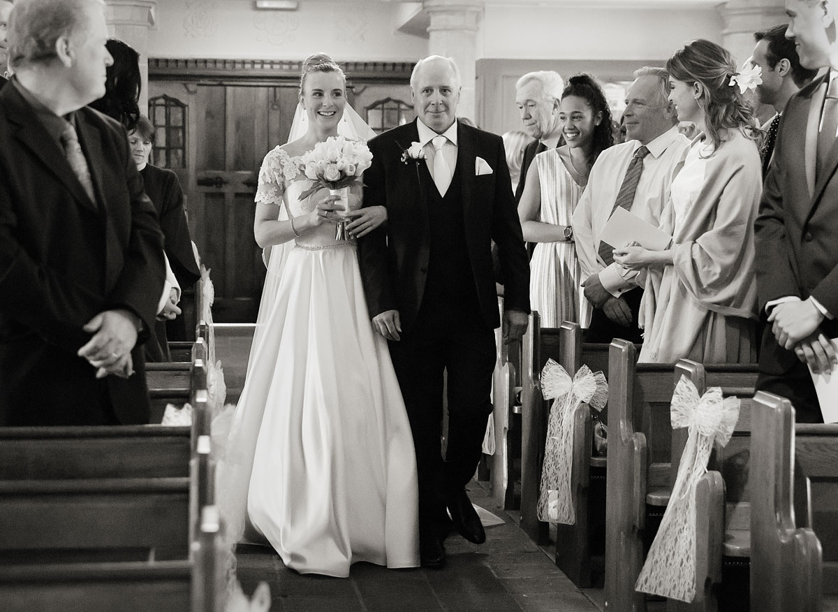 Bride-and-her-father-walk-down-the-aisle-for-church-wedding