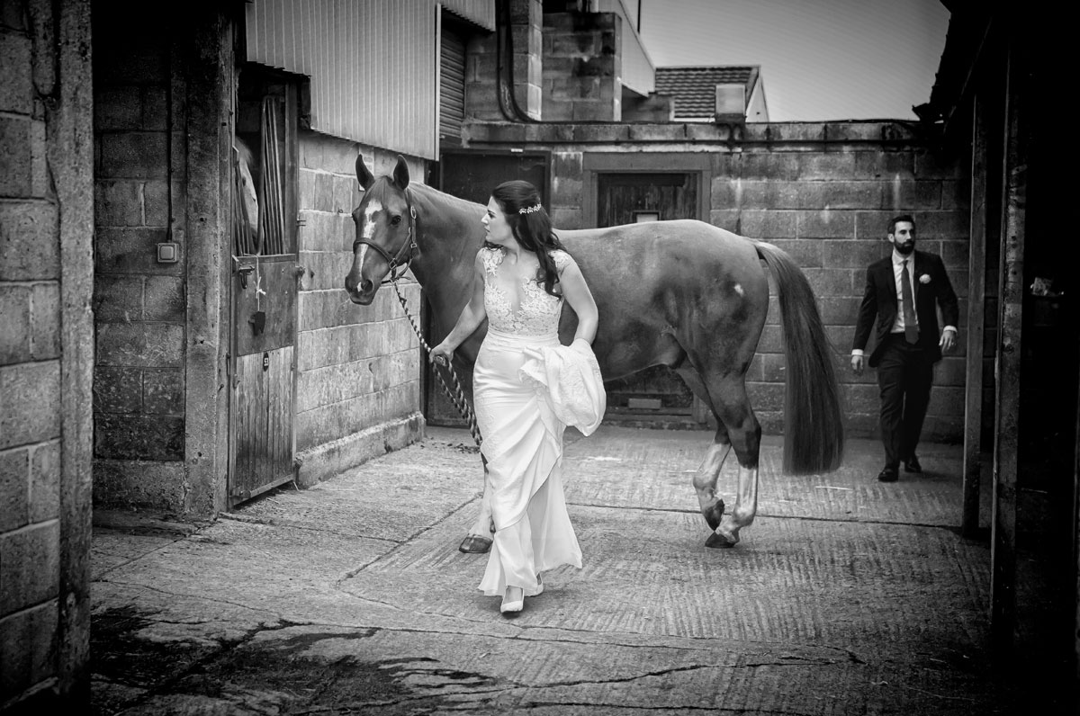 Chelsea-bride-leads-horse-in-stables-on-wedding-day-image