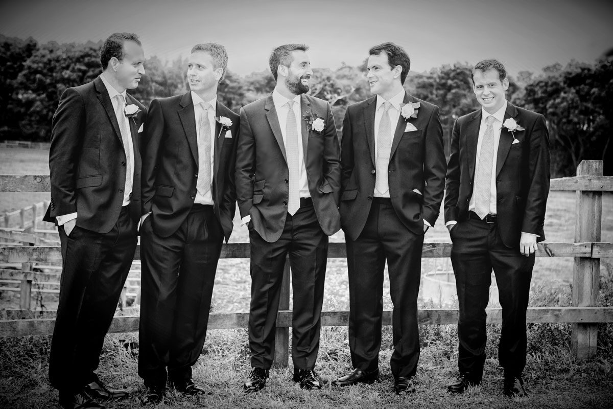 Groomsmen chat in field Enfield wedding reception