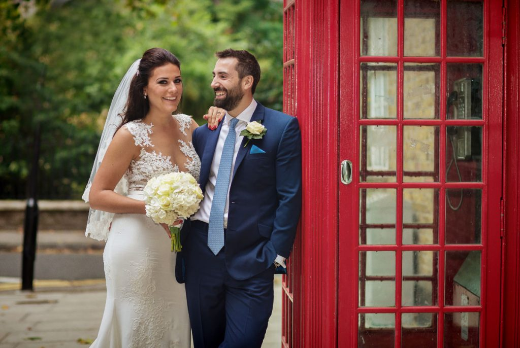 Wedding couple by red phone box Chelsea and St Lukes