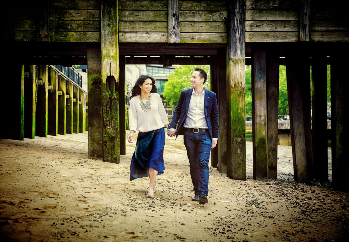 Engagement shoot couple walk on by Thames on Southbank
