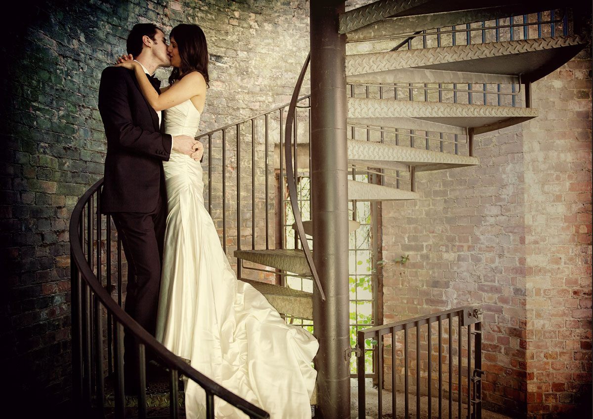 Wedding couple kiss on spiral staircase
