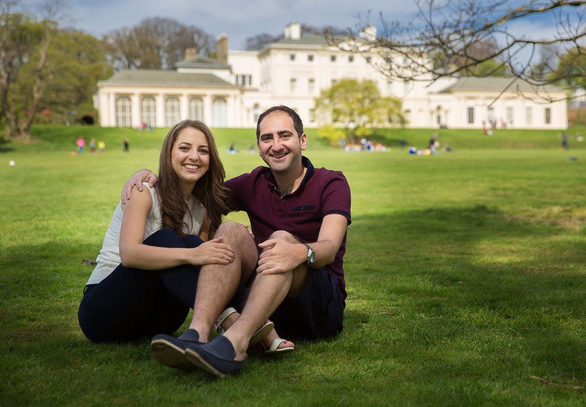 Engagement couple sit on grass at Kenwood House photo shoot