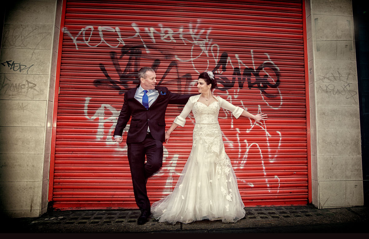 London bride and groom in front of red roller doors photo