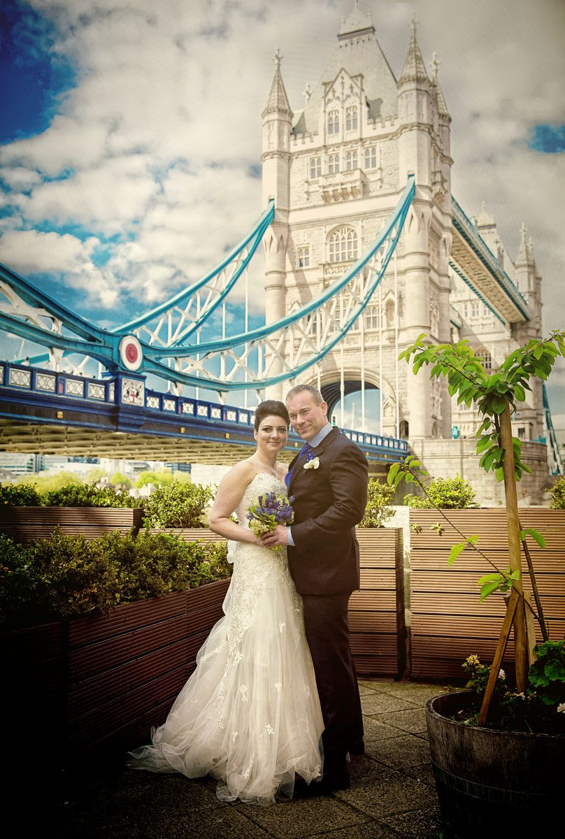 London wedding couple pose for photo by Tower Bridge