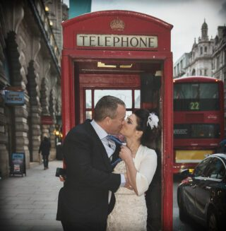Wedding couple kiss inside red London phone box image