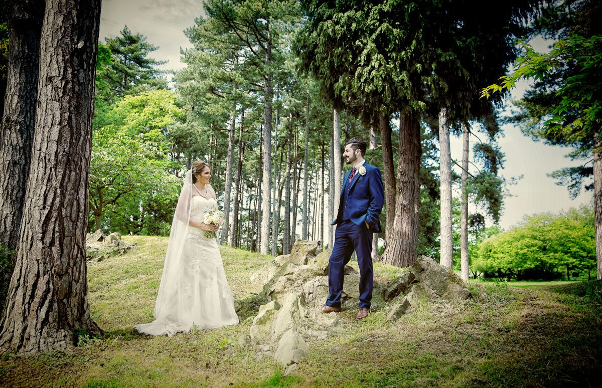 Bride and groom by trees at Fanhams Hall wedding