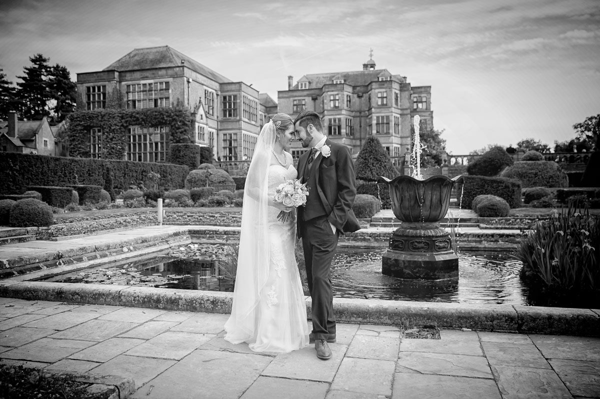 Bride and groom head to head in Fanhams Hall wedding garden in black and white