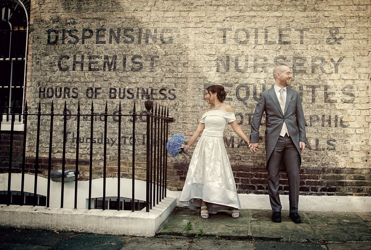 Couple hold hands by old wall for Islington Town Hall wedding photographers