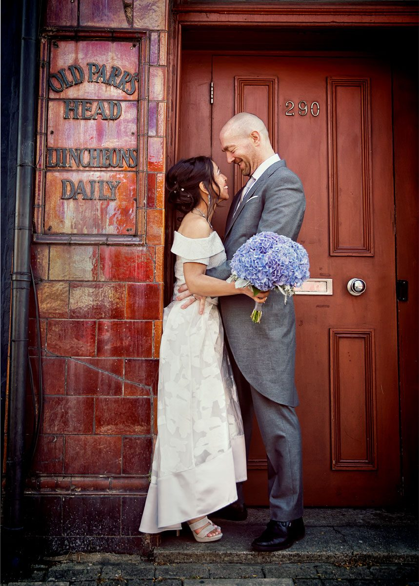 Couple hug in ornage doorway after Islington Town Hall wedding day