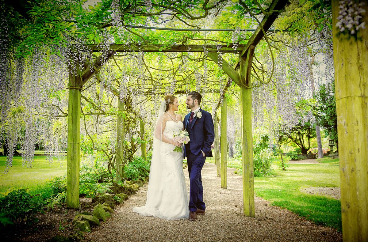 Fanhams Hall wedding bride and groom in wisteria garden image