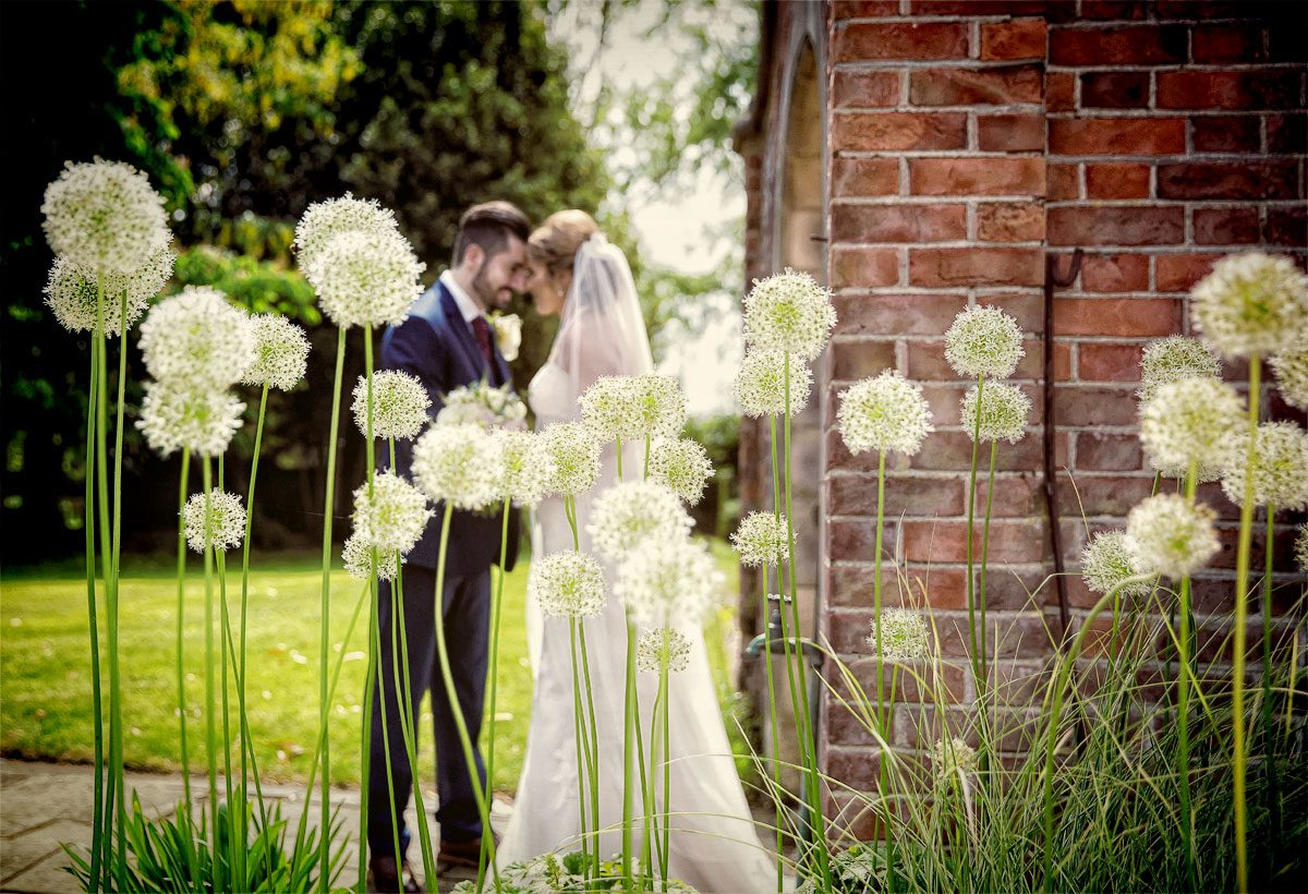 Flowers and wedding couple in grounds of Fanhams Hall