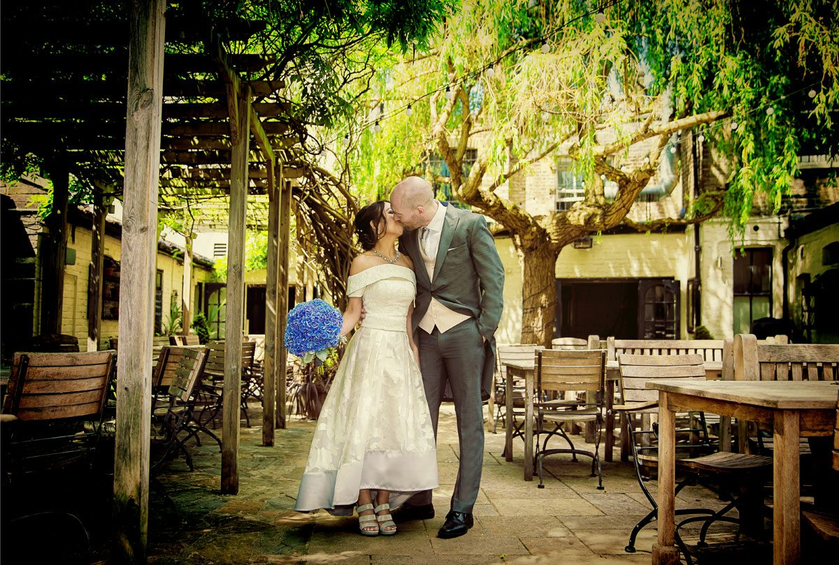 Wedding couple kiss in garden of Albion Pub Islington