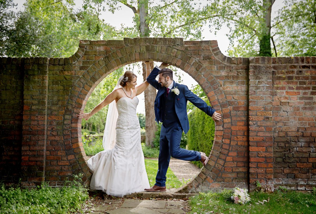 Wedding couple pose in hole in wall at Fanhams Hall