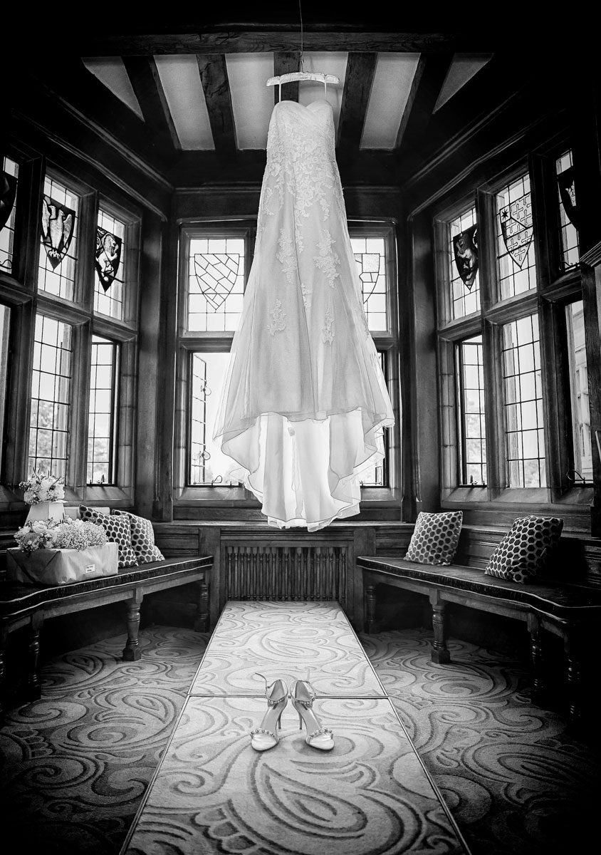 Wedding dress hanging in window at Fanhams Hall photoall