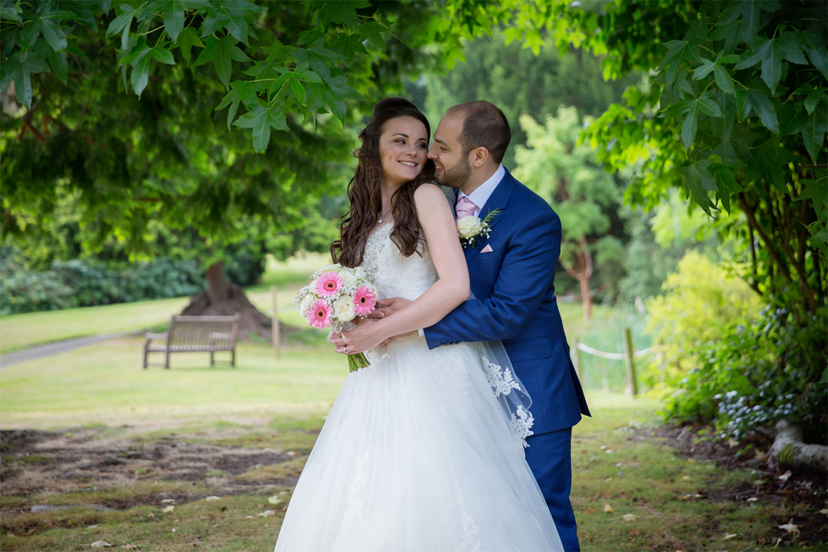 Bride and groom hug in gardens at Northcote House wedding