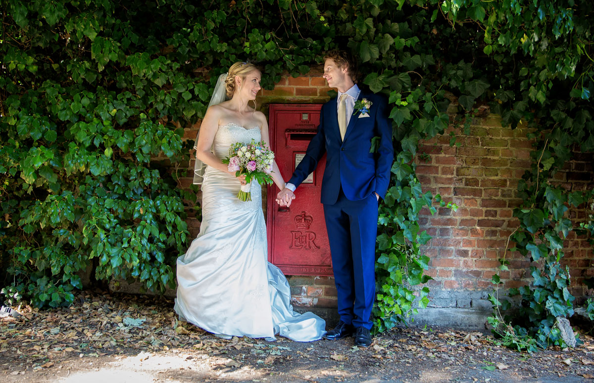 Barnet wedding couple hold hands by red post box