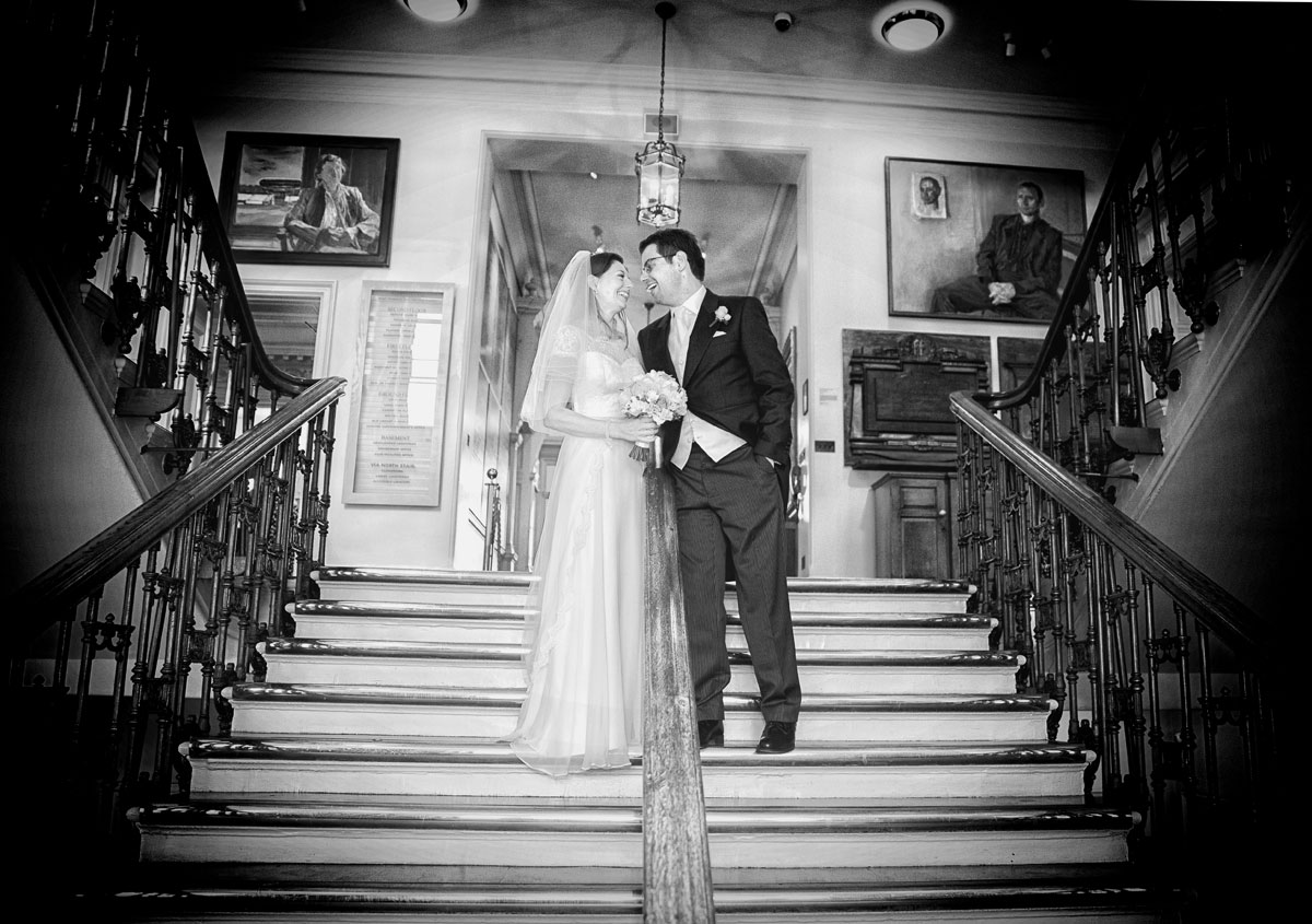 Bride and groom laughing on stairs at Lords Cricket Ground wedding day