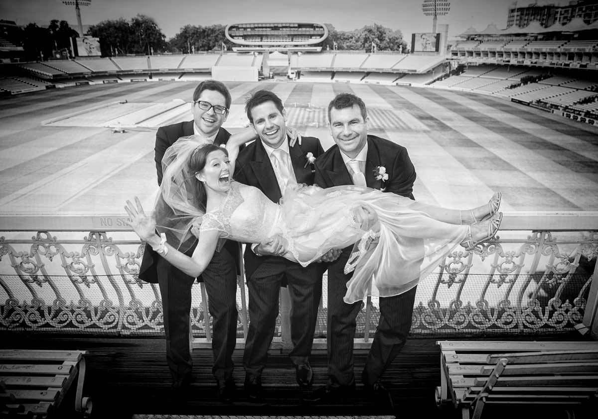 Groomsmen hold bride in stands at Lords Cricket Ground wedding