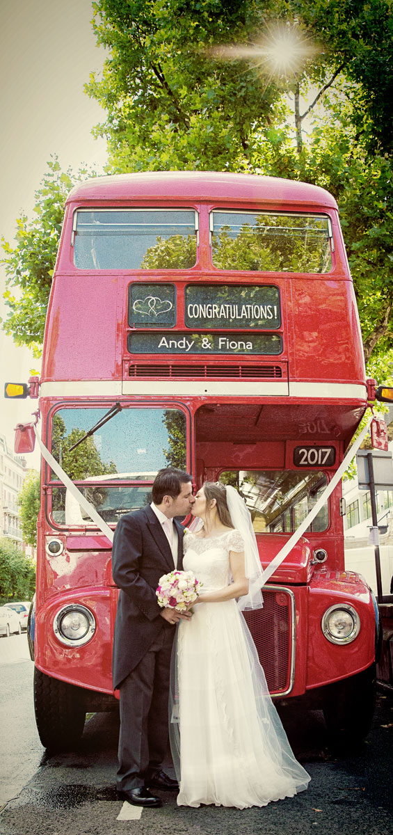 Kissing by London red bus at Lords cricket ground wedding