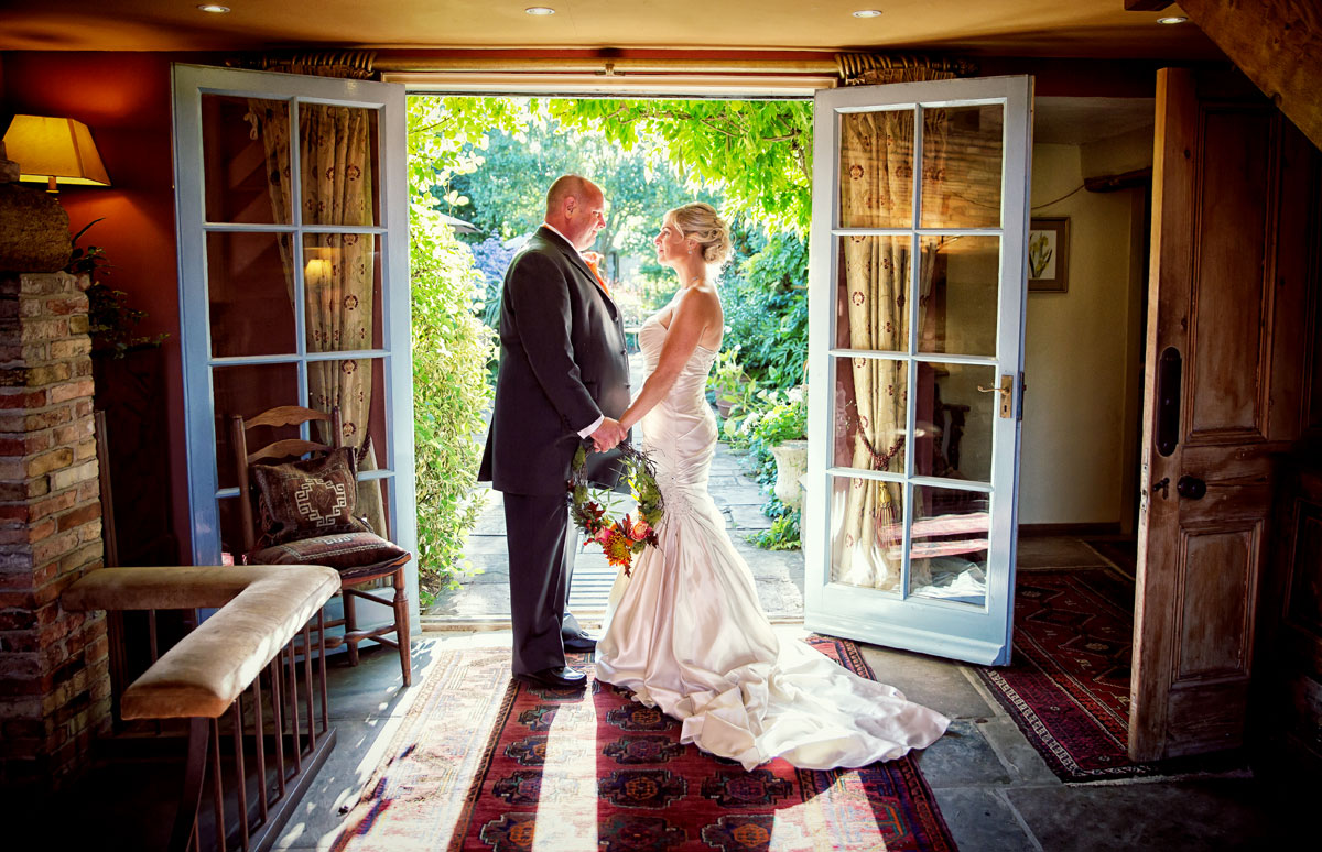 Couple hold hands at South Farm wedding in sunlit doorway