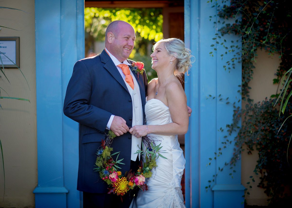 Couple laugh in doorway South Farm wedding
