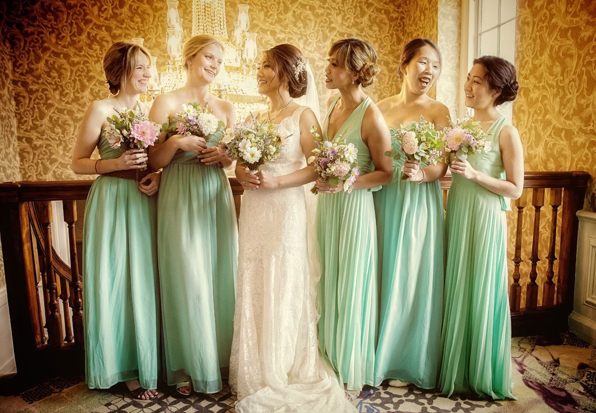 Bridesmaids talk and laugh by Stoke place Hotel chandeliers