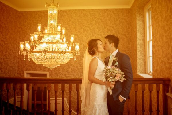 Wedding couple kiss by chandelier at Stoke Place Hotel