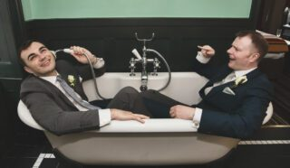 Two grooms in a bath after London wedding