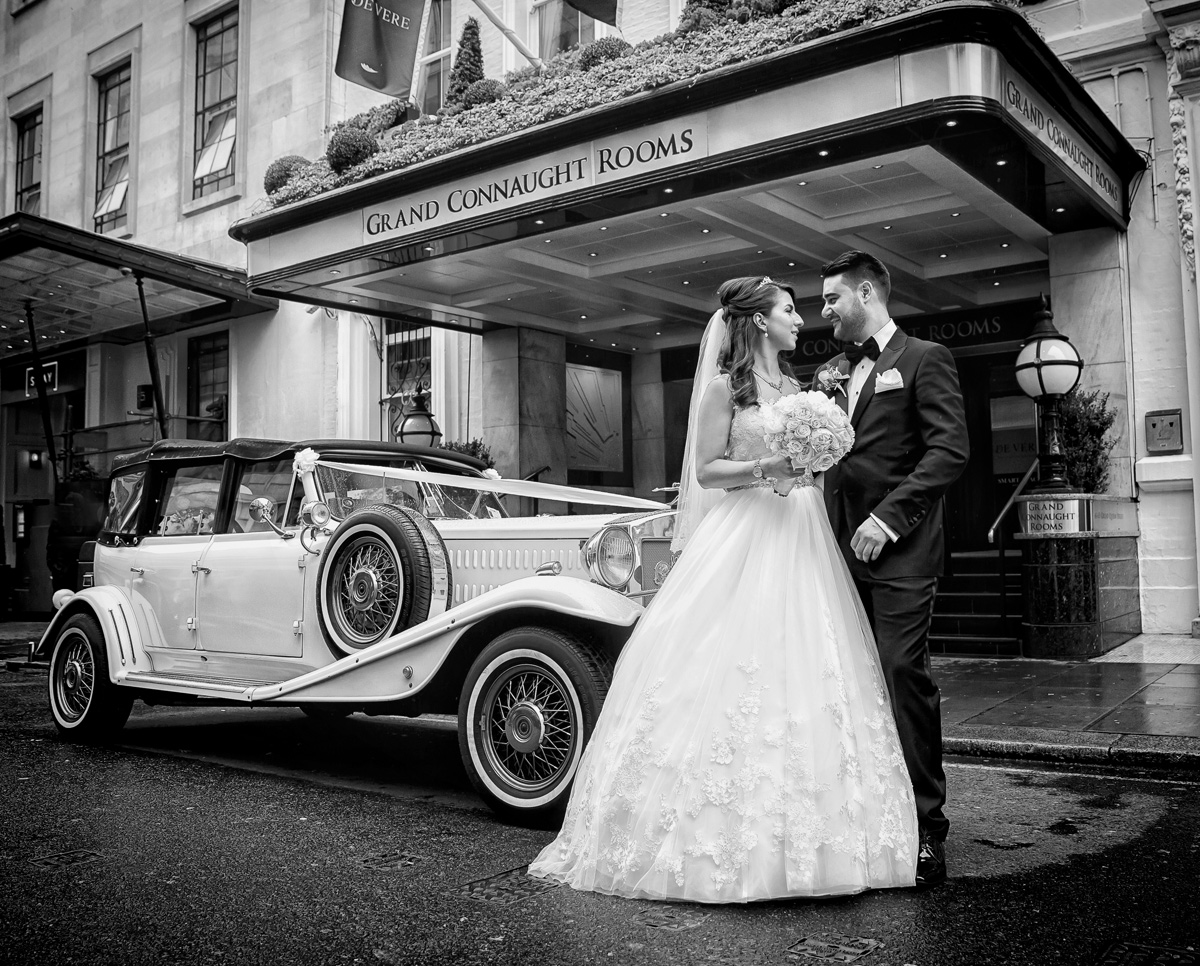 Bride groom and wedding car outside the Grand Connaught Rooms London