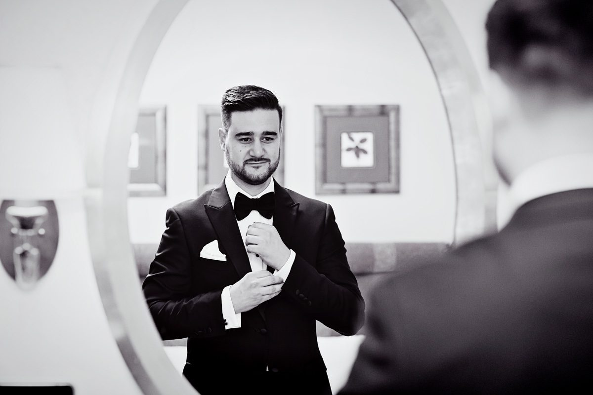 Groom gets ready in mirror for Connaught Rooms London wedding day