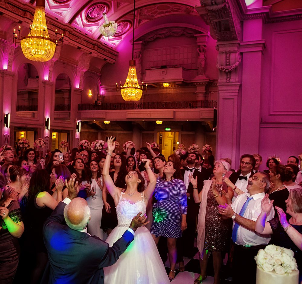 Tossing the bouquet at Connaught Rooms wedding reception