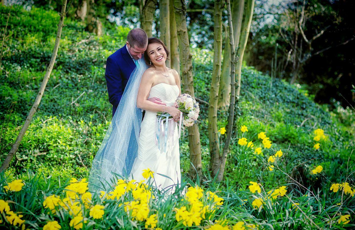 Bride and groom in daffodils at Hanbury Manor Wedding