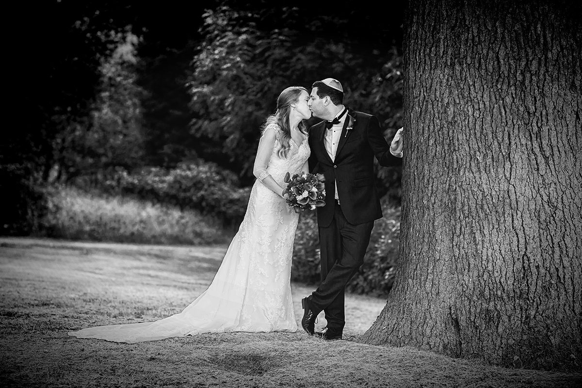 Bride and groom kiss by tree Shendish Manor wedding
