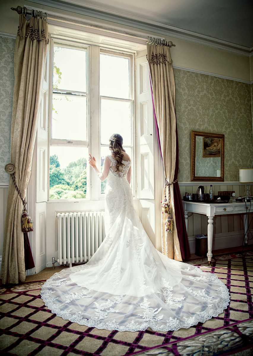 Bride looks out of window at her Shendish Manor wedding