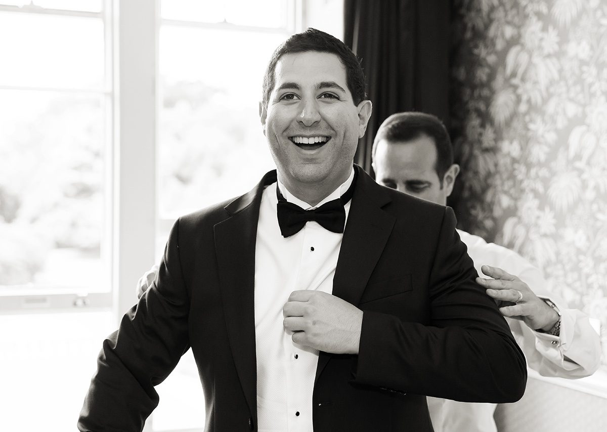 Groom laughs getting ready for Shendish Manor Hotel wedding