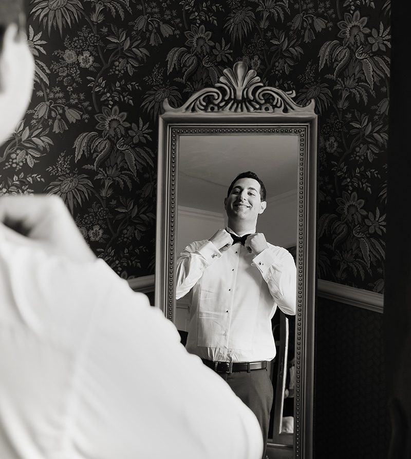 Groom by mirror Shendish Manor Hotel