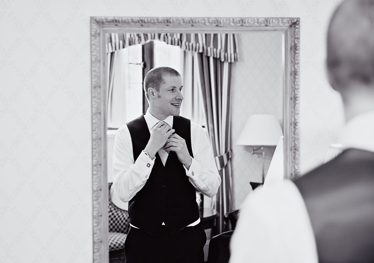 Groom gets ready in mirror for Hanbury Manor wedding