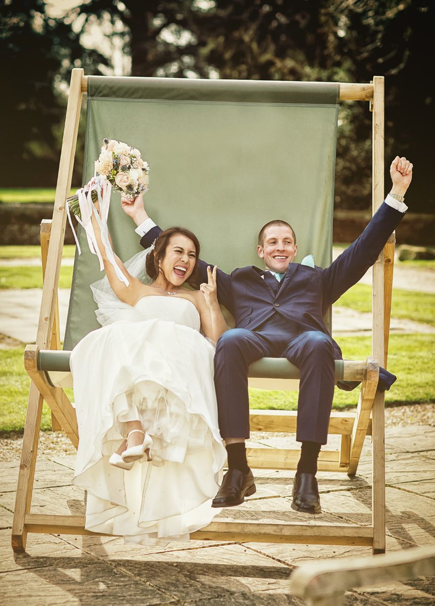 Wedding couple in big deckchair at Hanbury Manor
