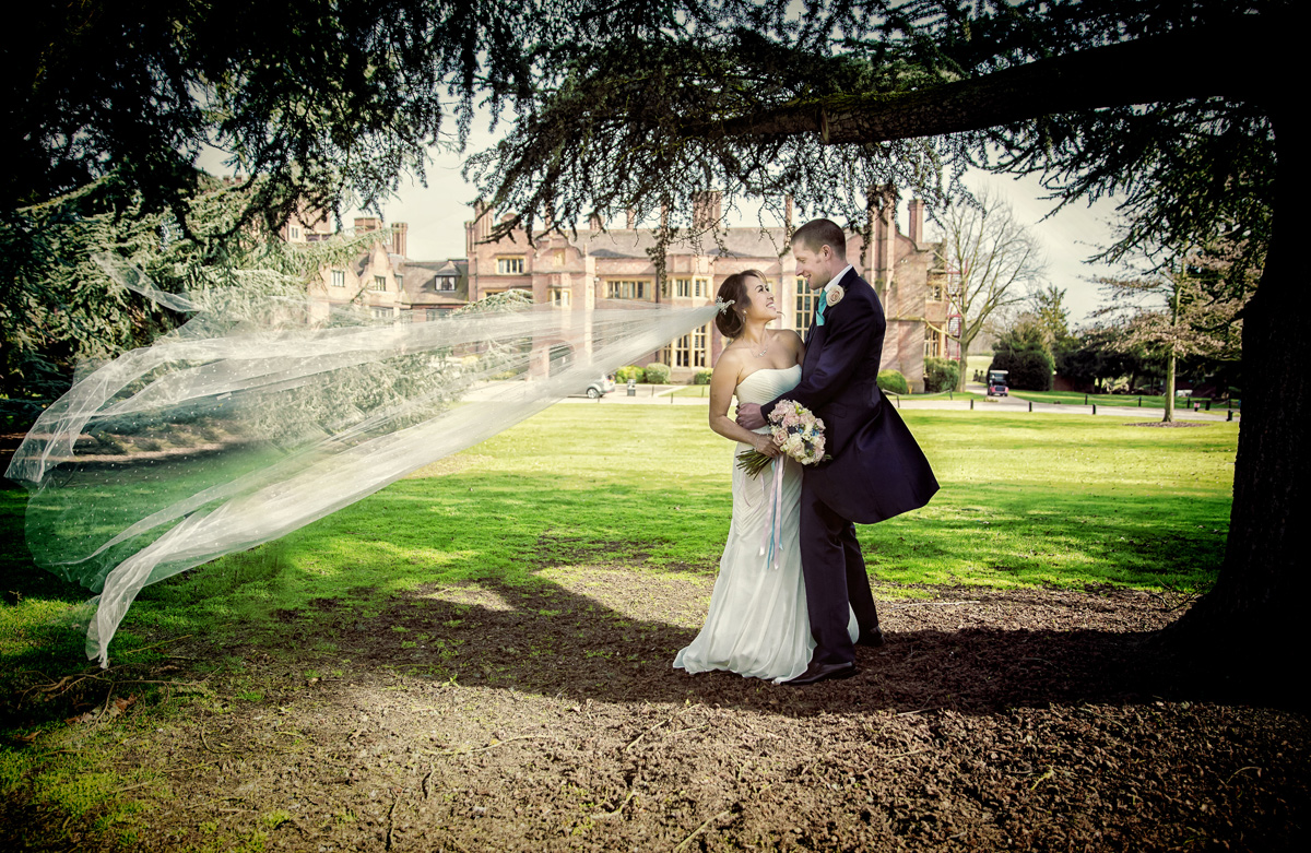 Bride's veil blows in wind at Hanbury Manor wedding Hertfordshire
