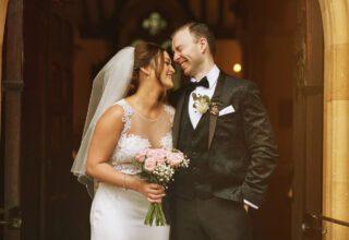 Bride and groom laugh in church doorway at London wedding