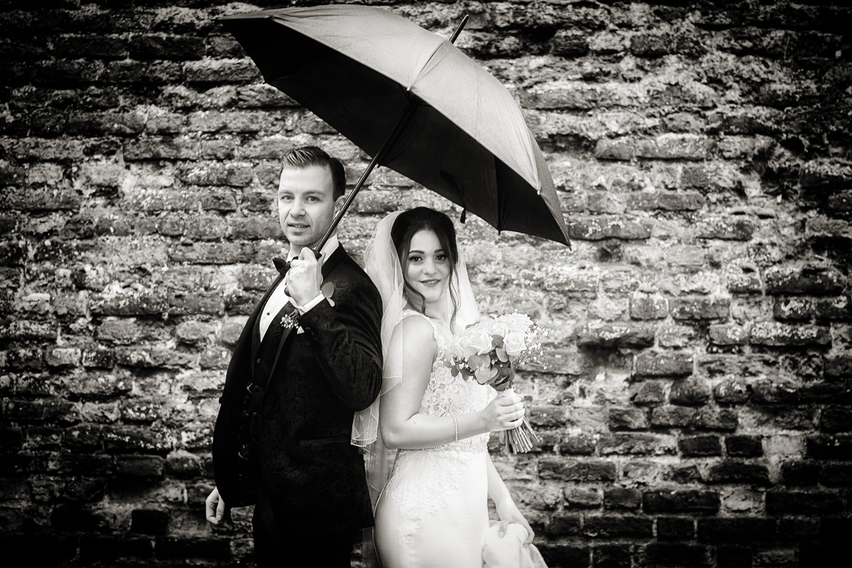 Bride and groom under umbrella after Southgate London wedding