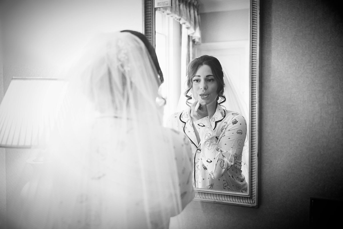 Bride gets ready with mirror West Lodge Park Hotel