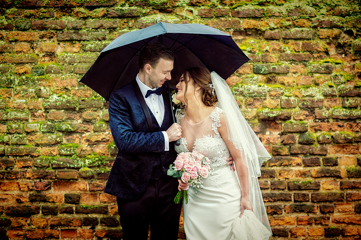 London wedding couple laugh together under umbrella
