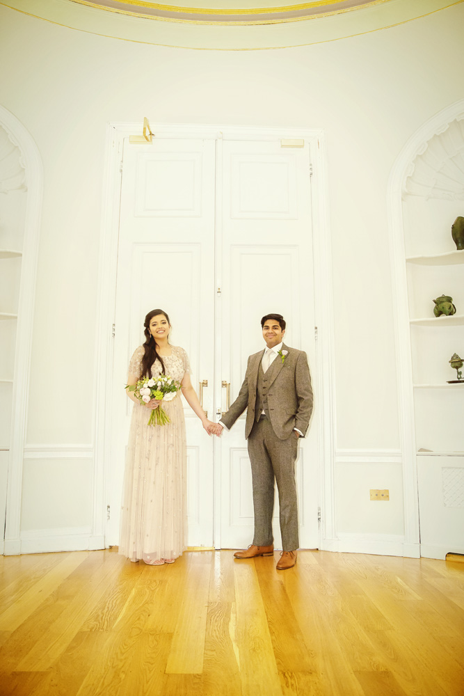 Bride and groom hold hands in Asia House London