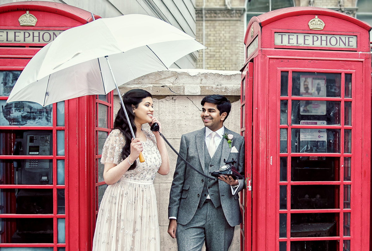 Langham Hotel wedding couple by red London telephone boxes with umbrella