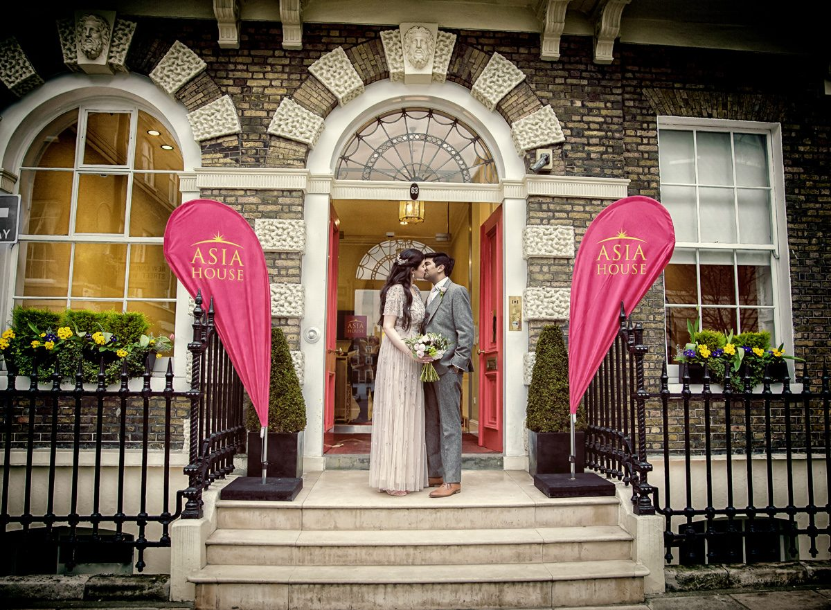 Wedding couple kiss in front of Asia House London
