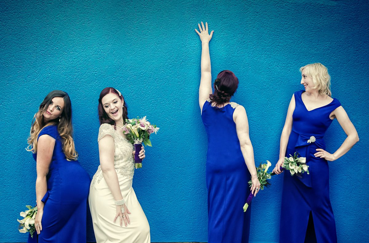 Islington wedding brides pose in front of blue wall London