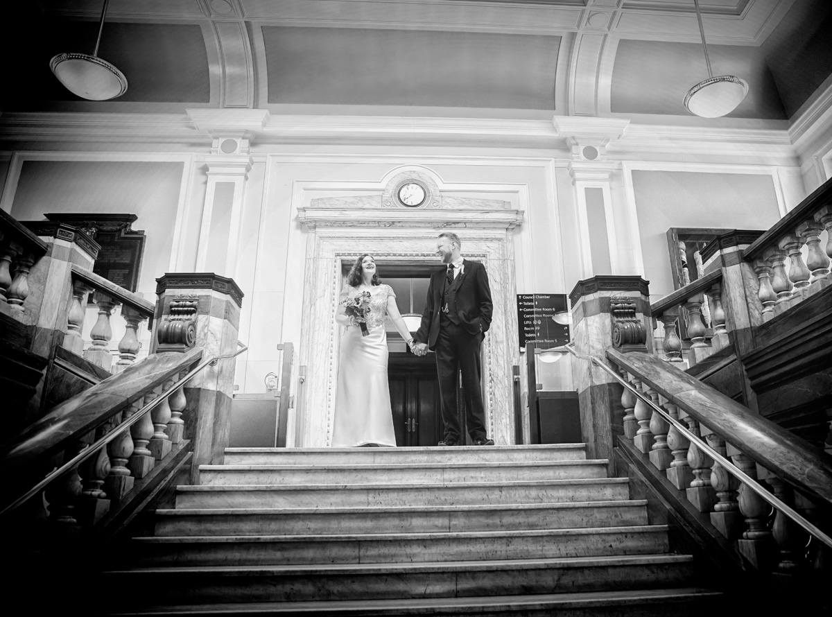 Bride and groom laugh at the top of Islington Town Hall stairs