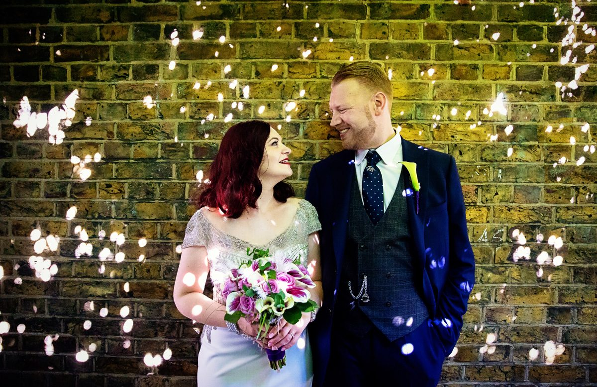Islington wedding couple by sunlit wall north London